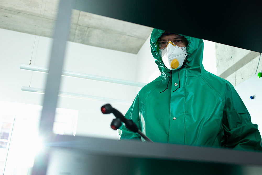 A man in green protective suit doing Fogging Spray Cleaning Services